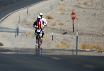 Charlie Engle, 50, runs through a mirage with his pace setter during the Badwater Ultramarathon in Death Valley National Park