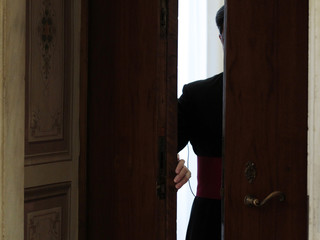 A prelate opens the door of Pope Benedict XVI's private library prior to the start of his meeting with Costa Rica's President Chinchilla at the Vatican