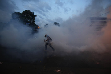 An anti-government protester carries a tear gas canister during clashes with police near the Government house in Bangkok