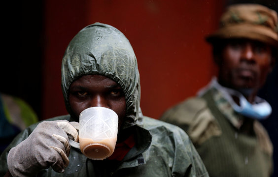 A volunteer drinks tea as he rests during the search for residents feared trapped in the rubble of a six-storey building that collapsed after days of heavy rain in Nairobi