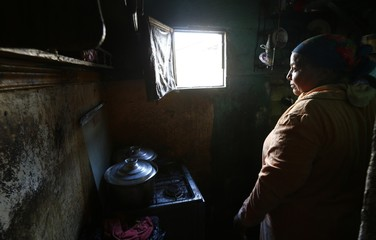 Om Mostafa, 50, cooks in her kitchen in the fishermen's village of the El Max area in the Mediterranean city of Alexandria