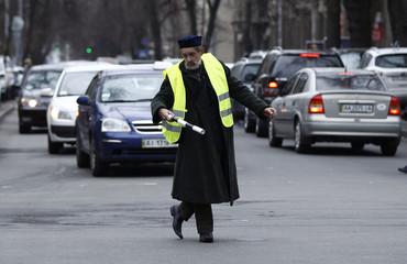 An anti-Yanukovich protester regulates traffic in central Kiev