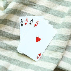 Four aces cards on stripe background