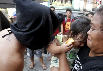 A hooded penitent talks to a girl during a break in a Holy Week ritual in Mandaluyong