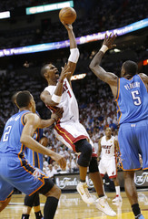Miami Heat's Bosh shoots between Oklahoma City Thunder's Sefolosha and Perkins in the first quarter during Game 4 of the NBA basketball finals in Miami