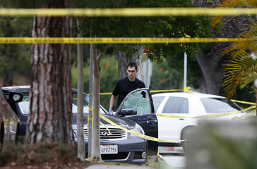 A police officer is seen by a bullet riddled car outside a home which was set on fire in Santa Monica