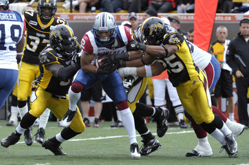 Alouettes running back Whitaker is tackled by Tiger-Cats defenders Williams and Knowlton during the first half of their CFL football game in Hamilton
