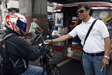 Paterno distributes condoms to a motorcyclist during a protest in Manila