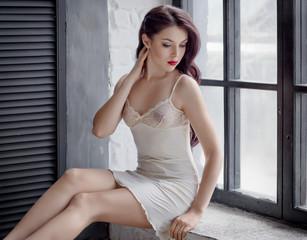Woman in a silk nightie on gray background