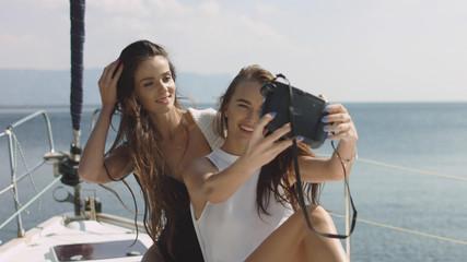 Best friends using camera and taking selfie on luxury sailing boat selfie