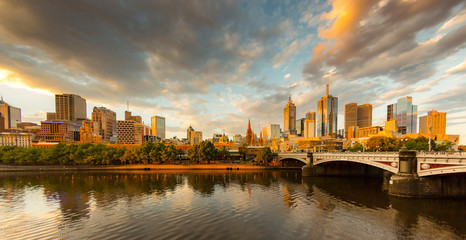 Melbourne City, Yarra River, Princes Bridge with Reflection Cityscape Skyline background under dramatic Golden Sky Sunset, Australia