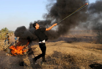A masked Palestinian protester uses a sling to throw stones at Israeli troops during clashes near the border between Israel and Central Gaza Strip