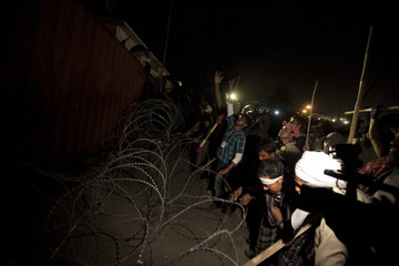 Supporters of Tahir ul-Qadri try to remove the barbed wire to get on top of the container barricade as they go towards the Prime Minister's house during Revolution March in Islamabad