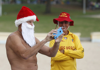Surf lifesaver Scott Williams wears a Santa beard and hat as he takes a picture of friends following an early morning ocean swim off Sydney's South Cronulla Beach on Christmas day