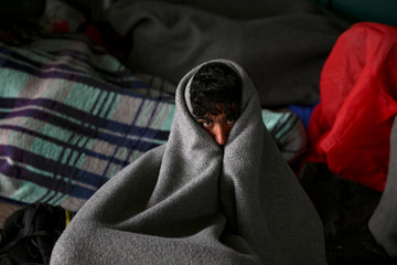 A migrant tries to warm himself up as refugees and migrants take a break at a petrol station before abandoning their trek to the Hungarian border, in the town of Indjija