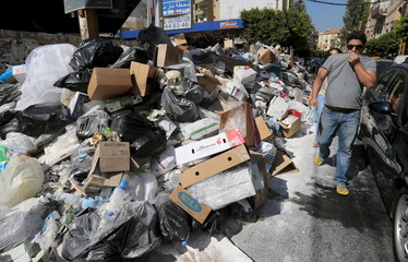 A man covers his nose as he walks past a pile of garbage along a street in Beirut, Lebanon