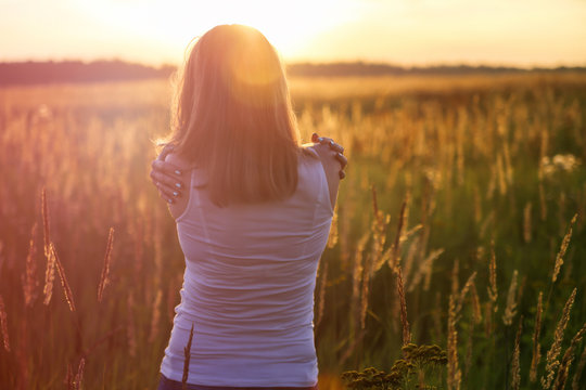 Young girl hugging herself on a sunny field. Instagram