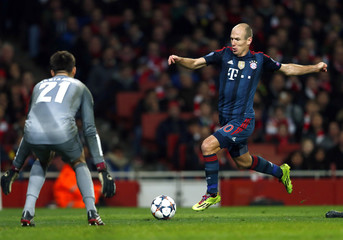 Bayern Munich's Robben challenges Arsenal's goalkeeper Fabianski during their Champions League round of 16 first leg soccer match at the Emirates Stadium in London