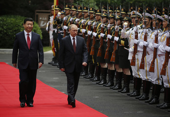 Russia's President Putin and China's President Xi review an honour guard during a welcoming ceremony at the Xijiao State Guesthouse ahead of the fourth CICA summit in Shanghai