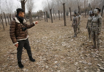 """Chinese artist Liu Bolin direct his models painted in camouflage colours to blend in with the background for his artwork """"Dongji"""", or Winter Solstice, in Beijing"""
