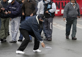 A worker from the Huanuni mine throws a dynamite stick during a protest rally in La Paz