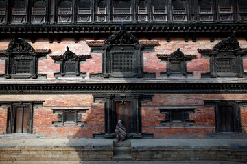 A woman sits at the courtyard of Durbar Square in Bhaktapur