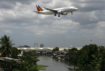 A Philippine Airlines (PAL) plane, the country's flag carrier, flies over a slum area in Manila