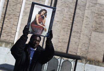 Lockheart, from Plainsfield, New Jersey, holds photo of Houston behind police barricade blocks away from Hope Baptist Church in Newark
