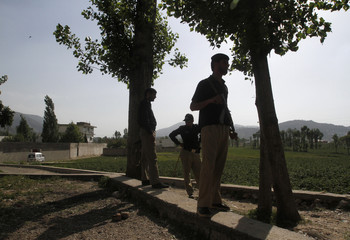 Policemen stand guard under trees near the compound (background) where al Qaeda leader Osama bin Laden was killed in Abbottabad Pakistan