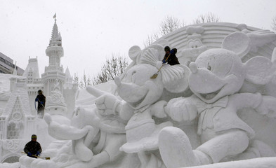 Japan's Self-defense force army soldiers clear snow on snow sculpture at snow festival in Sapporo