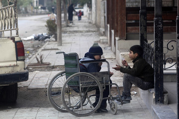 A child on a wheelchair rests on a street in Eastern Ghouta of Damascus