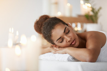 Tender african girl resting relaxing with closed eyes in spa salon.