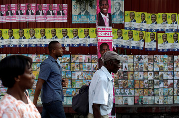 People walk next to electoral posters plastered on a wall beside movies on display for sale in a street of Port-au-Prince, Haiti