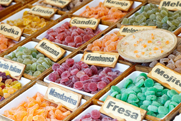 Colorful candied fruits assortment with a signs saying: lemon, watermelon, peach, apple, raspberry, mojito, Mandarin and strawberry.