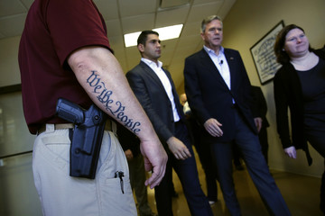 Bush walks past a security guard with a sidearm and a tattoo of the start of the preamble to the U.S. constitution, after a town hall meeting with employees at FN America gun manufacturers in Columbia, South Carolina