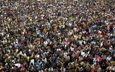 Thousands of Catholics pray during a Palm Sunday mass at a town square in Bogota