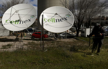 A worker uses a lawnmower next to telecom antennas of Spain's telecoms infrastructures firm Cellnex in Madrid