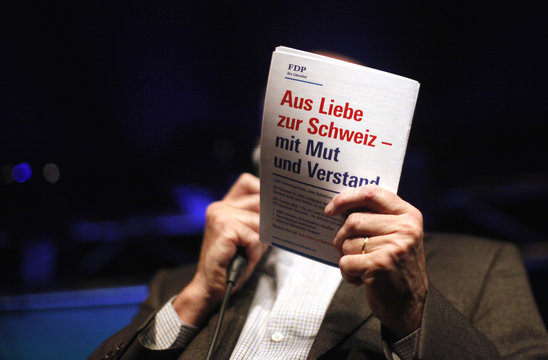 Switzerland's Liberal Free Democratic Party President Pelli shows a brochure during a media event in Bern