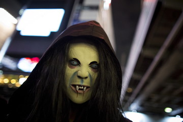 A reveller wearing a mask poses for pictures during Halloween celebrations in the Shibuya district in Tokyo, Japan