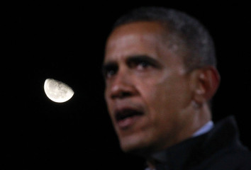 U.S. President Barack Obama is pictured alongside a partial moon during a night time outdoor election campaign rally in Aurora