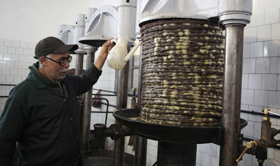A worker pours hot water during a process to press olive paste at a traditional olive oil processing factory in Tebourba