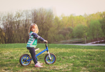 little girl riding bike in nature