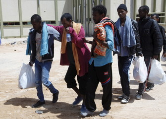 Migrants help another migrant walk to a bus bound for an immigration centre in the coastal city of Misrata, Libya