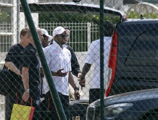 Olympique Lyon's Govou walks with soccer team as they leave their Gerland training center in Lyon