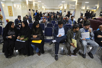 Iranians wait before registering as candidates for Iran's parliamentary elections in Tehran