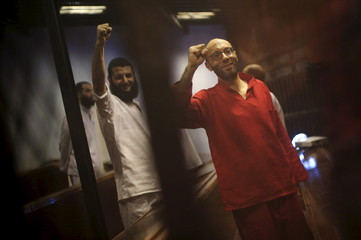 Former presidential office manager Ahmed Abdel-Ati, shouts solgans behind bars at a court wearing the red uniform of a prisoner sentenced to death, during his court appearance with Muslim Brotherhood members on the outskirts of Cairo, Egypt