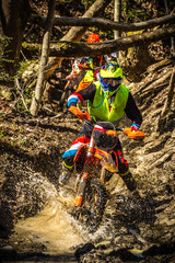 A motocross rider passes under a fallen tree on a crosscountry race