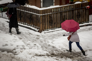 People make their way through the snow during the morning rush in the Park Slope section of Brooklyn, New York