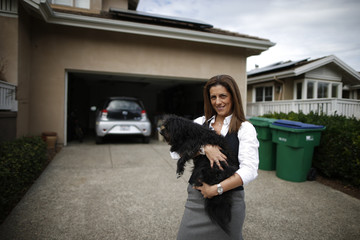A computer science professor stands next to her home and her electric car in Irvine, California