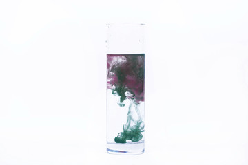 Green and pink paint fall in a glass with water